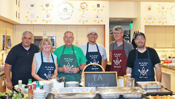 Group wearing PA Freemason aprons standing together in kitchen