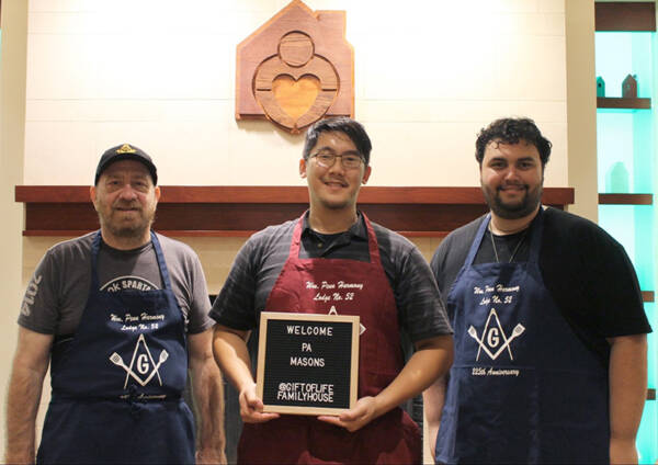 Three men wearing PA Mason aprons with welcome sign